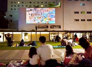ホテルフジタ福井の外壁を活用した野外映画上映会。多くの市民がくつろいだ=10月5日夜、福井県福井市中央公園