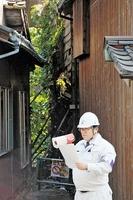 草に覆われた空き家(奥)取り壊しの行政代執行を宣言する福井県越前町の職員=12日、同町梅浦