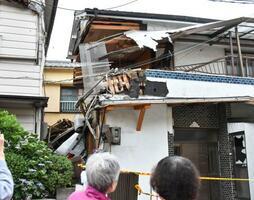 住宅に突っ込んだ乗用車(左下)=31日午後、和歌山市