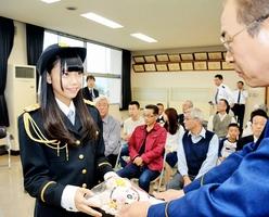 にこやかに委嘱状を受け取る長久玲奈さん(左)=9日、福井県警坂井署