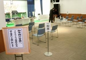 参列者に廻り焼香を呼び掛ける掲示。一般席の椅子は数を絞っている=福井県福井市のソートフル新田塚