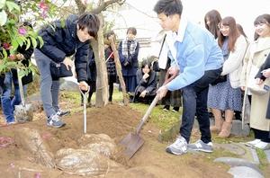 タイムカプセルを掘り起こす新成人=1月12日、福井県福井市円山小