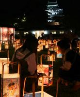 「松江水燈路」でライトアップされた松江城(後方)の周辺を幻想的に照らすあんどん=22日夜、松江市