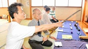 森國清廣さん(左)に鑑賞のこつを教わりながら、刀剣美術に親しむ参加者=14日、福井市社北公民館