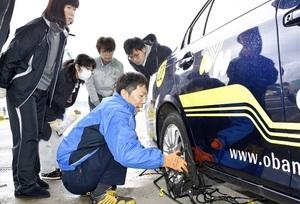 樹脂製チェーンの装着法を小浜自動車学校の職員(中央)から学ぶ参加者=12月17日、福井県小浜市府中の同校