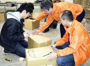 段ボールの簡易トイレ作りに挑戦する男性(左)=3月、福井県福井市の福井県産業会館