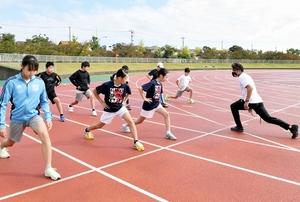 猿山力也選手(右)から速く走るための基礎練習を教えてもらう児童たち=10月11日、福井県坂井市の三国運動公園陸上競技場