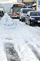 圧雪ででこぼこになった道路を蛇行しながら通行する車の列=14日午後4時50分ごろ、福井市高柳1丁目