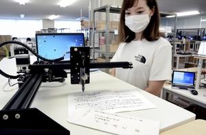 データを基に、自動で便せんに文字を書くロボット=福井県鯖江市上河端町の「エクネス」
