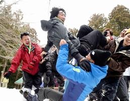 雪の斜面を目がけて放り投げられる厄年の男性=2月3日、福井県鯖江市尾花町の禅定神社