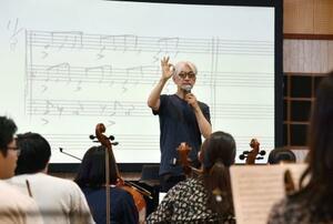東北ユースオーケストラの合宿で、演奏を指導する坂本龍一さん=8月11日、山梨県富士河口湖町