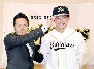 由田慎太郎スカウト(左)から帽子をかぶせてもらい笑顔をみせる山崎颯一郎=福井県敦賀市のニューサンピア敦賀