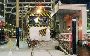 今シーズン初めて出動し、路面電車のレールに積もった雪を掃き飛ばす「ササラ電車」=15日早朝、札幌市