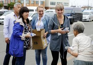 北海道むかわ町の避難所を訪れ、飲料水を配る「ビザなし交流」のロシア側訪問団の女性=22日午後