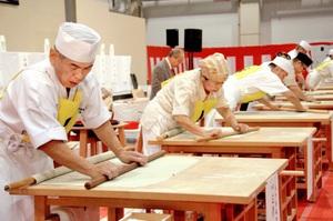 麺棒でそばを丁寧に延ばす出場者=20日、福井市の県産業会館