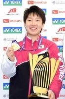 優勝メダルを手に笑顔で会見に臨む山口茜選手=18日夜、成田空港