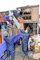 全焼した住宅の後片付けを手伝う福井工業大学の学生ら=2月6日、福井県福井市