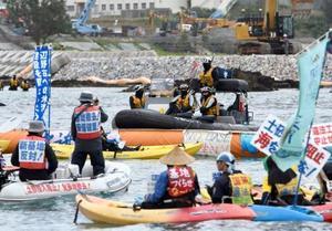 埋め立てが進む沖縄県名護市辺野古沿岸部の海上で、米軍普天間飛行場の辺野古移設に反対し抗議する人たち。奥は警戒する海上保安庁のボート=16日午前
