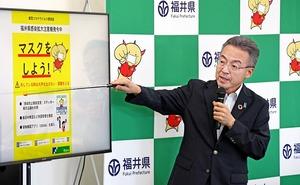 マスク着用などを呼び掛ける福井県のポスターについて説明する杉本達治知事=8月4日、福井県庁