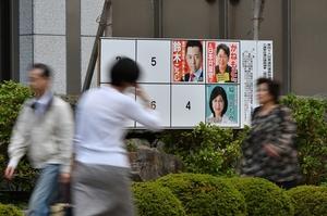 衆院選のポスター掲示場のそばを通り過ぎる人たち=10日、福井市大手3丁目