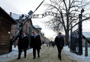 アウシュビッツ強制収容所跡の門をくぐる生存者=1月、ポーランド・オシフィエンチム(ロイター=共同)