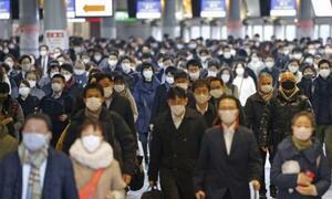 マスクを着けて通勤する人たち=2月、東京・JR品川駅