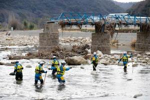 広島県三原市で行われた行方不明者の一斉捜索。後方には崩落した橋が残る=6日午前