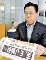 福井新聞ウェブ号外に目を通し、厳しい表情を浮かべるシャルマンの宮地正雄社長=24日、福井県鯖江市の同社本社