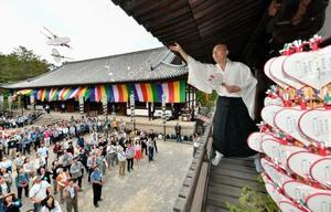 唐招提寺の「うちわまき」で鼓楼からうちわ「宝扇」をまく僧侶=19日午後、奈良市