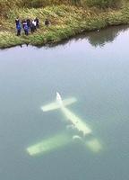 航空事故調査員ら(左上)が調べた不時着した小型機=16日午後2時55分ごろ、福井市小尉町上空から日本空撮・小型無人機ドローンで撮影