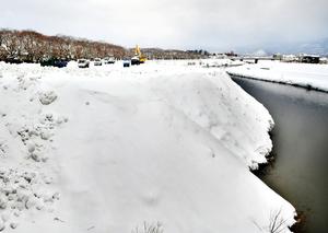 排雪でいっぱいになった足羽川河川敷の雪捨て場=12日午前8時50分ごろ、福井市有楽町