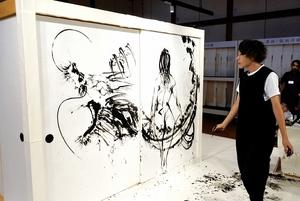 観衆の見守る中、越前和紙の大ふすまに女性と竜を描き上げた西元祐貴さんのライブペインティング=9月7日、福井県越前市の紙の文化博物館