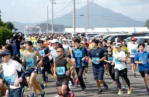青葉山を背にスタートする10キロの部のランナー=10月27日、福井県高浜町和田