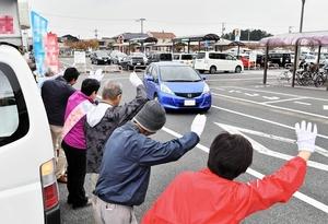 量販店近くの街頭でドライバーに手を振り、支持を訴える候補者ら=21日、福井市飯塚町