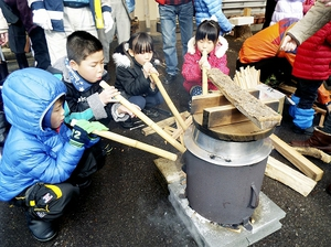 竹筒でかまどに息を吹き込む子どもたち=30日、福井県越前市都辺町