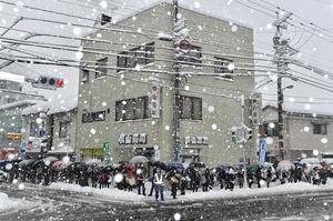雪が激しく降る中、交差点で試験会場に向かうため列をつくった受験生=13日午前8時ごろ、福井市の福井大学正門前