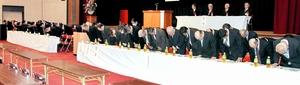昨年発覚したJA福井市の巨額着服事件を受け、総代会の冒頭で一斉に頭を下げる役員や職員=25日、JA福井市本店