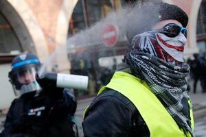 11日、フランス・パリで行われた年金制度改革案に対するデモで、参加者(右)に催涙ガスを噴射する警察官(AP=共同)