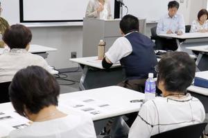 「引き出し屋」による被害を受けた女性(壇上)の話に聞き入る親たち=23日午後、東京都大田区