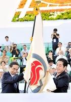 総合閉会式で愛媛県の中村時広知事(右)から国体旗を引き継ぐ福井県の西川一誠知事=松山市のニンジニアスタジアム