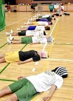 腹式呼吸でリラックスするトレーニングを実践する仁愛女子高バスケットボール部員。顔にタオルをかけて集中力を高めて行っている=同校体育館