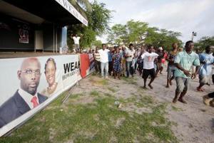 選挙の結果に沸くジョージ・ウェア氏の支援者たちとキャンペーンの横断幕=19日、モンロビア(ロイター=共同)