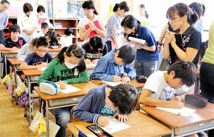 性別疑惑が持ち上がった陸上選手に思いをはせながら手紙を書く児童=23日、福井市松本小