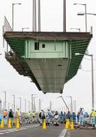 撤去のため、クレーン船でつり上げられる関西空港連絡橋の橋桁=12日午後