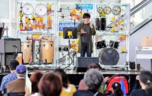 打楽器の演奏ロボットを背に熱唱する出演者=10日、福井市のハピテラス
