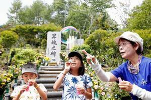 日航ジャンボ機墜落事故から35年を迎え、「昇魂之碑」の前で犠牲者を悼み、遺族関係者の孫たちとシャボン玉を飛ばす美谷島邦子さん(右)=12日午前、群馬県上野村