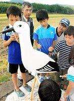 コウちゃん像に色を塗る白山小児童と、それを見守る同校OB=27日、福井県越前市都辺町