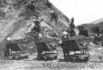 土砂を満載したトロッコを押す 作業員。馬車や人が担いで物 を運んでいた時代に、トロッコ は最新鋭の運搬機械だった。