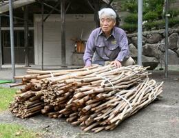 男性が届けた約340本のつえと「御巣鷹の尾根」管理人の黒沢完一さん=18日、群馬県上野村