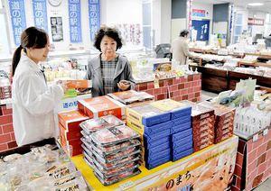 道の駅「越前」でスタッフ(左)からお薦めの土産品を教えてもらう観光客=福井県越前町